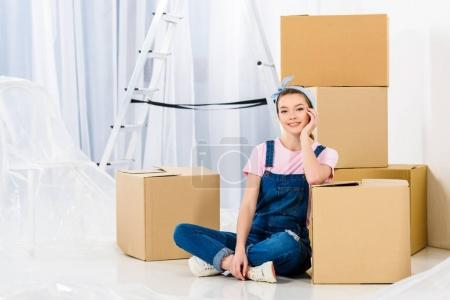 happy girl resting chin on hand and leaning on box