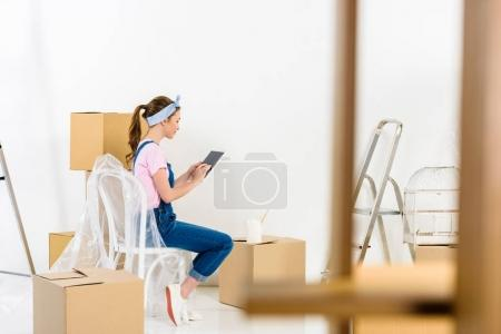 side view of girl using tablet after moving to new home
