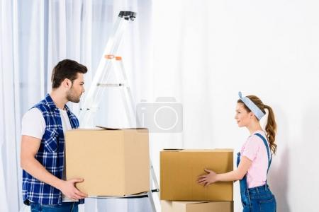 Photo for Boyfriend and girlfriend moving boxes and looking at each other - Royalty Free Image