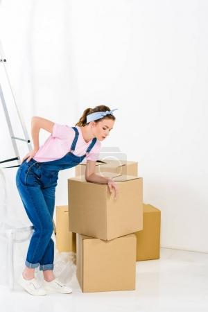 girl with pain in back after moving heavy boxes