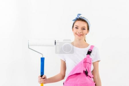 smiling girl standing with paint roller brush