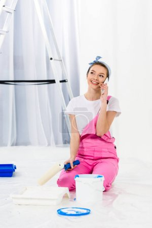 smiling girl sitting with paint roller brush and talking by smartphone