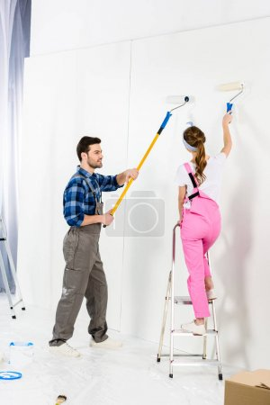 boyfriend and girlfriend painting wall with white paint