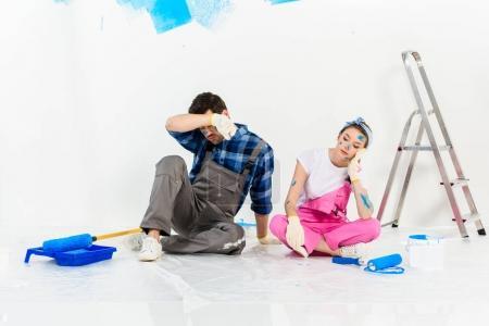 Photo pour Fatigué de copain et copine assis sur le plancher pendant les réparations - image libre de droit