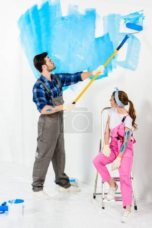 boyfriend painting wall and girlfriend sitting on ladder