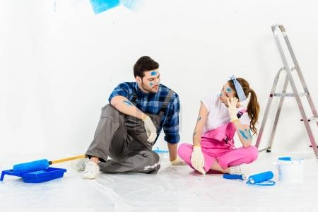 boyfriend and girlfriend sitting on floor in room with repairs