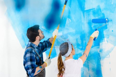 Photo for Boyfriend and girlfriend painting wall with blue paint - Royalty Free Image