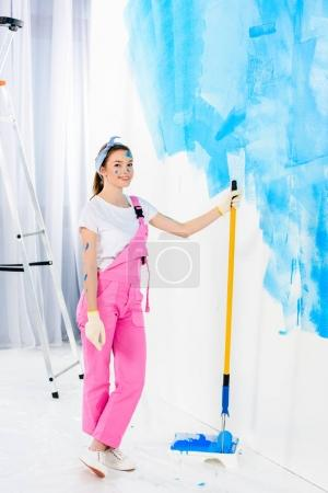 smiling girl holding paint roller brush and looking at camera