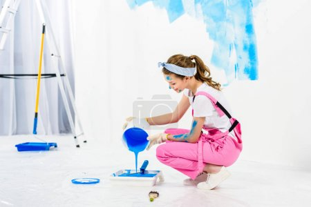 girl pouring paint from bucket into plastic paint tray