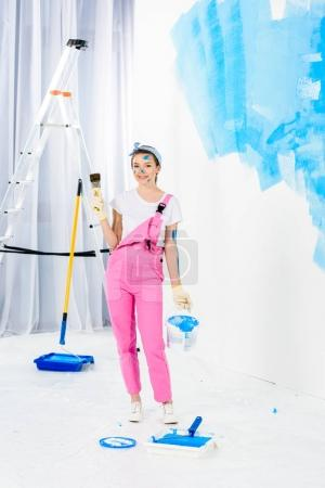 smiling girl holding paint brush and bucket with paint