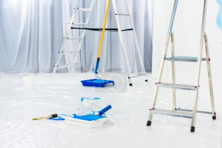 ladders and paint roller brushes in blue paint in room