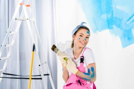 smiling girl holding paint brush and looking at camera