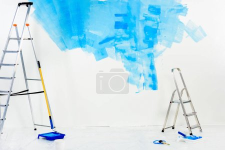 Photo for Ladders and paint roller brushes in blue paint - Royalty Free Image