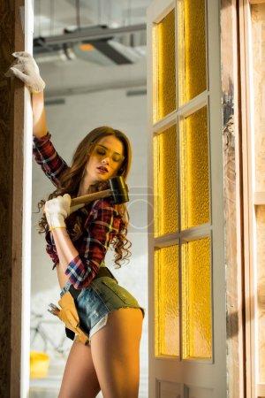 Photo pour Femme de travail sexy avec ceinture à outils et marteau posant sur la construction - image libre de droit