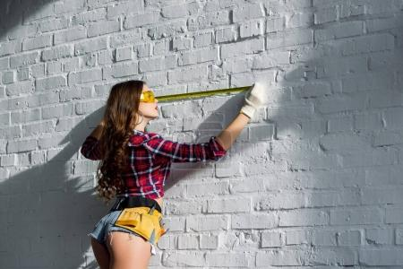 sexy woman with tool belt measuring white brick wall