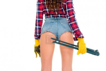 back view of sexy girl in gloves holding adjustable wrench, isolated on white