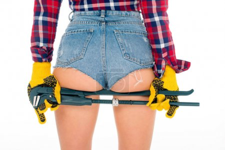 back cropped view of girl with sexy buttocks holding adjustable wrench, isolated on white