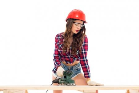 Photo for Sexy girl in hardhat working with grind tool at wooden table, isolated on white - Royalty Free Image