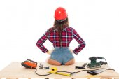 back view of sexy girl in hardhat sitting on wooden table with tools, isolated on white