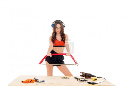 sexy girl with bow saw standing at wooden table with tools, isolated on white