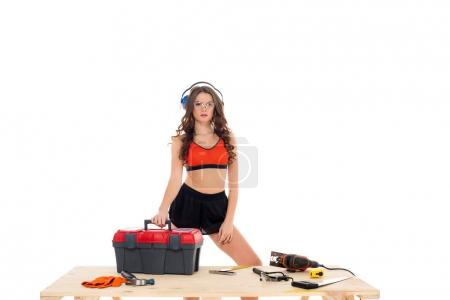 sexy girl in protective headphones standing at wooden table with toolbox and equipment, isolated on white