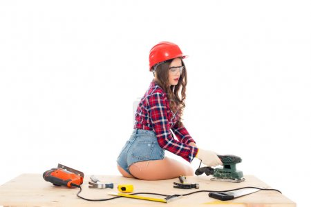 sexy girl in hardhat working with grind tool on wooden table with tools, isolated on white