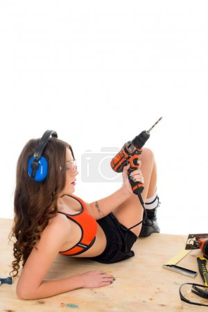 seductive girl in protective headphones posing with electric drill at wooden table with tools, isolated on white
