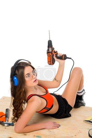 Photo pour Fille sexy dans des écouteurs de protection posant avec perceuse électrique à la table en bois avec des outils, isolé sur blanc - image libre de droit