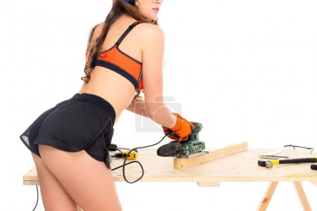 Photo for Cropped view of girl in hardhat working with grind tool at wooden table with tools, isolated on white - Royalty Free Image