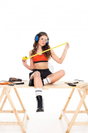 sexy girl in protective headphones sitting on wooden table with tools, isolated on white