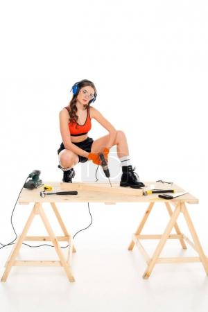 girl in protective headphones working with electric drill at wooden table with tools, isolated on white