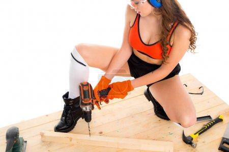 Photo pour Fille sexy en casque protecteur travaillant avec perceuse à table en bois, isolé sur blanc - image libre de droit