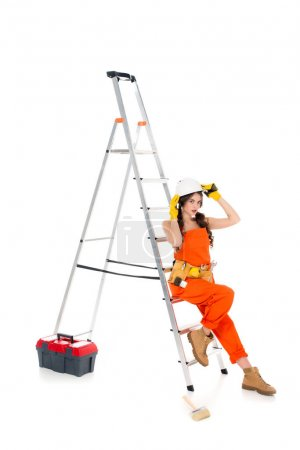 beautiful workwoman in overalls and safety helmet near ladder and toolbox, isolated on white