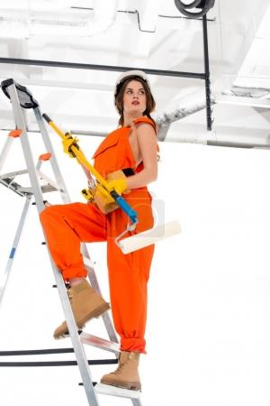 brunette workwoman in overalls and hardhat holding painting roller while standing on ladder