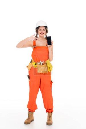 Photo pour Souriant workwoman en uniforme pointant sur smartphone avec écran blanc, isolé sur blanc - image libre de droit