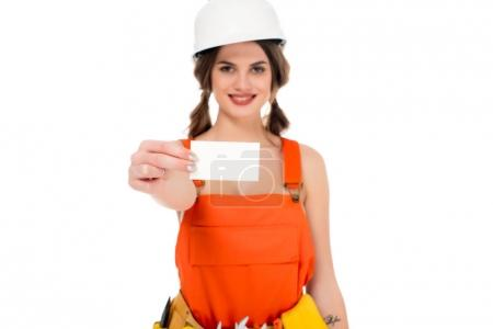 smiling workwoman in uniform and hardhat holding business card, isolated on white