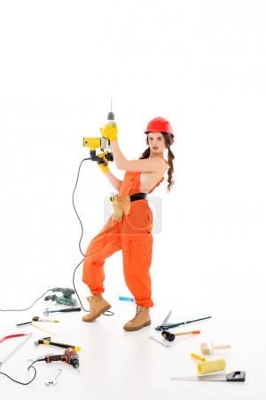 Photo pour Workwoman dans des combinaisons avec des perceuses électriques, différents outils gisant sur le sol, isolé sur blanc - image libre de droit