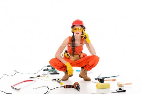 workwoman in overalls sitting on floor with different equipment and tools, isolated on white