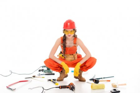 confident workwoman in overalls sitting on floor with different equipment and tools, isolated on white