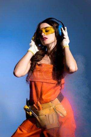 Foto de Hermosa chica en monos con cinturón de herramientas, gafas y auriculares de protección, aislados en azul - Imagen libre de derechos