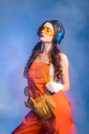 sexy girl in overalls with tool belt, goggles and protective headphones, isolated on blue with smoke