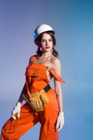 beautiful sexy in overalls and safety helmet with tool belt and goggles, isolated on blue