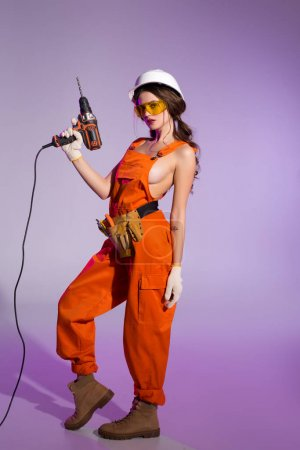 attractive girl in overalls and safety helmet with tool belt holding electric drill, on purple