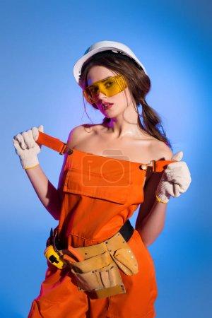 Foto de Chica seductora en guardapolvos uniformes y seguridad casco, aislado en azul - Imagen libre de derechos
