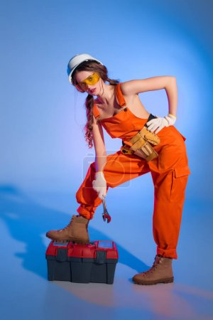 attractive girl in overalls uniform with tool belt and toolbox, on blue
