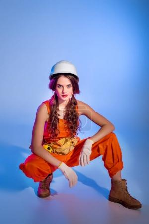 beautiful girl in overalls and safety helmet, on blue