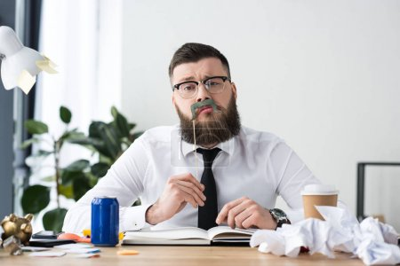 portrait of bearded businessman with party decoration sitting at workplace in office