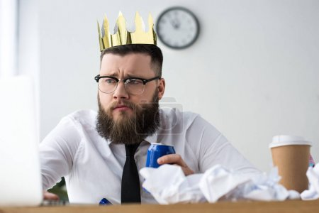 portrait of businessman with paper crown on head and soda drink at workplace in office