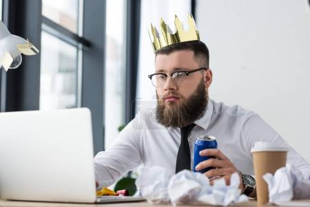portrait of businessman with paper crown on head and soda drink in hand working on laptop at workplace in office