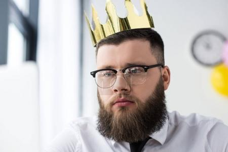 portrait of bearded businessman in eyeglasses with paper crown on head